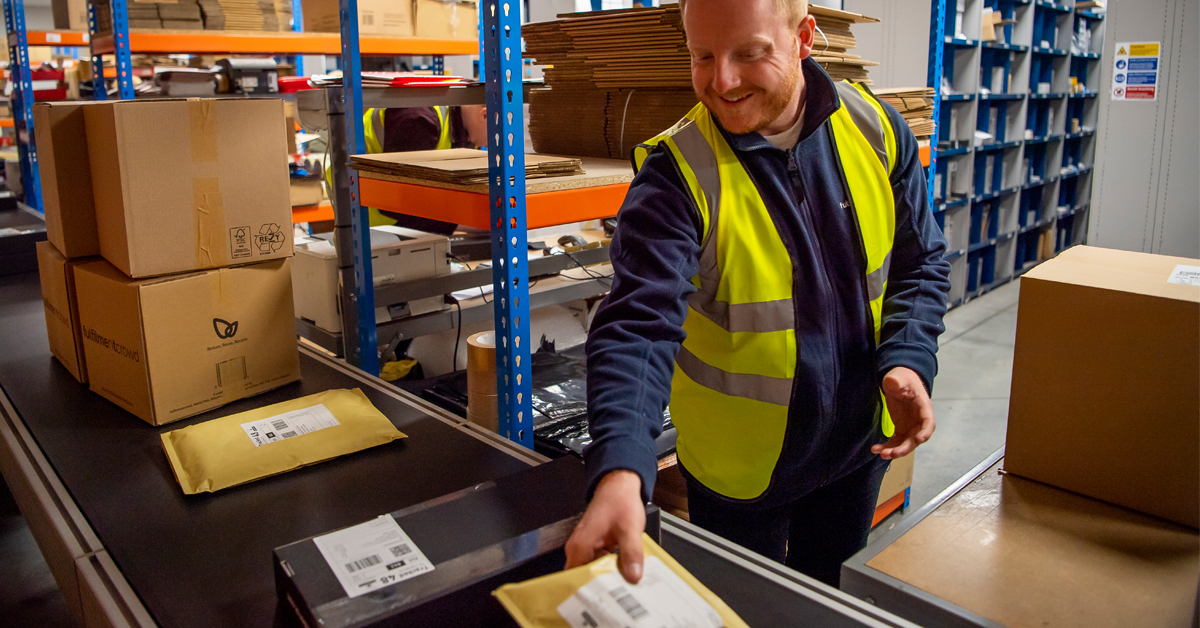 Happy warehouse operator placing packages on conveyer belt in fulfilment warehouse
